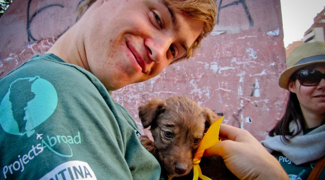 Voluntario de cuidado animal en Argentina llevando a un cachorro a un día comunitario para ayudarlo a encontrar un nuevo hogar.